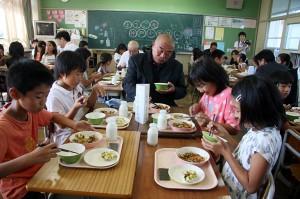 生産者と一緒に給食を食べる児童